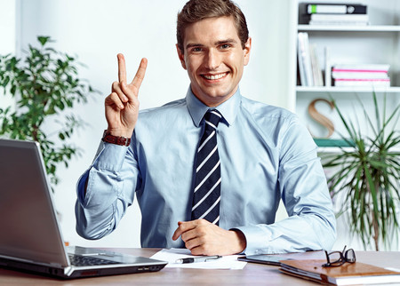 Successful businessman showing victory sign. Photo of young man working in the office. Business concept Reklamní fotografie