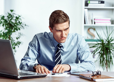 Angered worker with unhappy of facial expression. Photo of young man working in the office. Business concept Reklamní fotografie