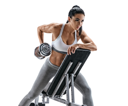 Athletic woman doing exercise with dumbbell leaning on sports bench. Photo of latin woman in fashionable sportswear isolated on white background. Strength and motivation