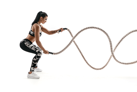Strong muscular woman working out with battle ropes. Photo of attractive woman in fashionable sportswear isolated on white background. Strength and motivation. Side view. Reklamní fotografie