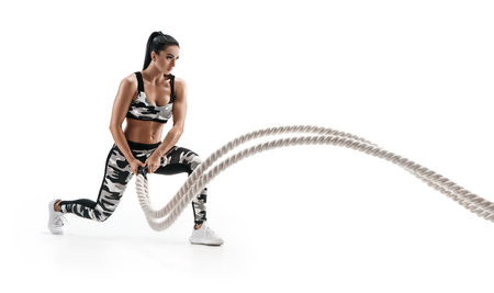 Muscular woman working out with heavy ropes. Photo of sporty woman in military sportswear isolated on white background. Strength and motivation. Side view Reklamní fotografie