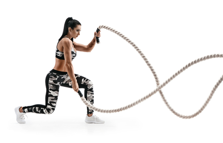 Strong woman workout with battle ropes. Photo of latin woman in military sportswear isolated on white background. Strength and motivation. Side view. Reklamní fotografie