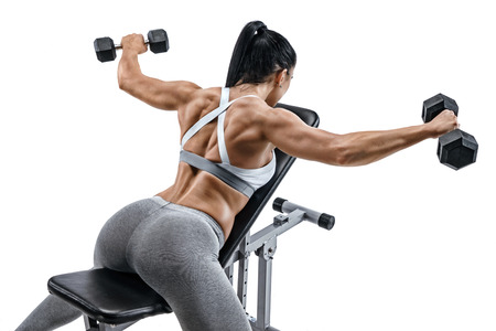 Muscular woman doing exercise with dumbbells for muscles of back. Photo of latin woman with good physique lying on sports bench isolated on white background. Strength and motivation
