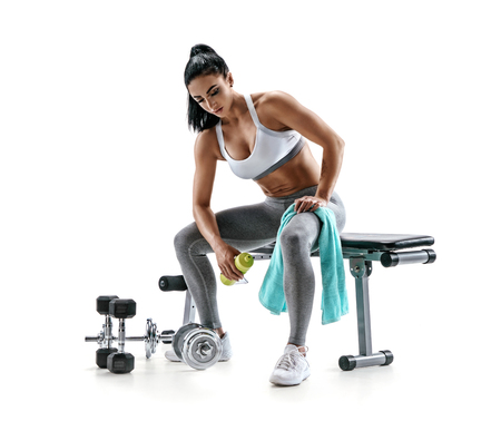 Resting time. Tired sporty woman resting after training. Photo of fitness model with towel and protein cocktail in shaker, sitting on sports bench isolated on white background. Sports and healthy lifestyle