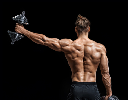 Bodybuilder doing exercise with heavy weight dumbbells. Rear view of young man with good physique on black background. Strength and motivation.