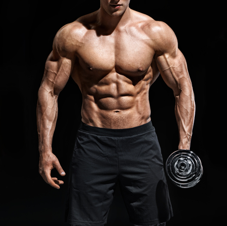 Close up of man showing muscular body and six pack abs. Photo of man shirtless with dumbbell on black background. Strength and motivation