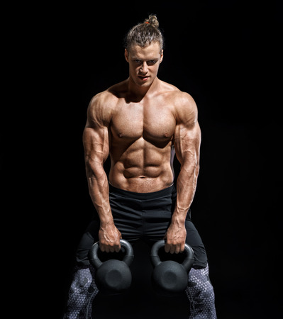 Young athletic man working out with a kettlebells. Photo of strong male with naked torso on black background. Strength and motivation Reklamní fotografie