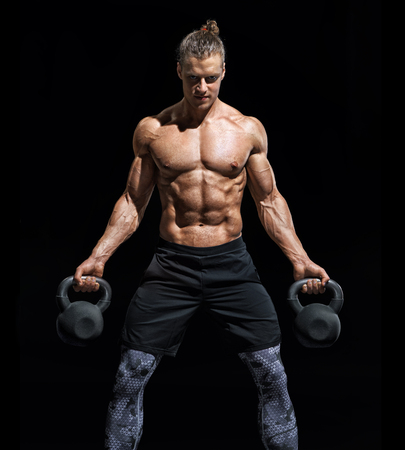 Sporty young man working out with a kettlebells. Photo of muscular man with naked torso on black background. Strength and motivation Reklamní fotografie