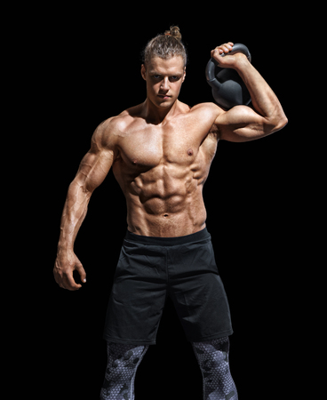Sporty young man working out with a kettlebell. Photo of muscular man with perfect physique on black background. Strength and motivation