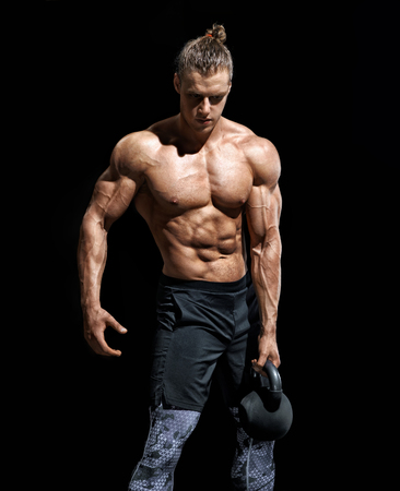 Young man having a break. Photo of muscular man with kettlebell on black background. Strength and motivation.