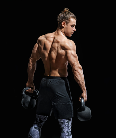 Strong man with kettlebells. Photo of muscular male with naked torso on black background. Strength and motivation. Rear view