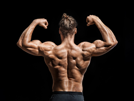 Young man showing his muscles. Rear view of bodybuilder with perfect physique on black background. Strength and motivation.