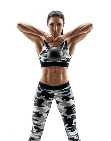 Sporty woman doing exercises with kettlebell. Photo of latin woman in military sportswear isolated on white background. Strength and motivation Reklamní fotografie