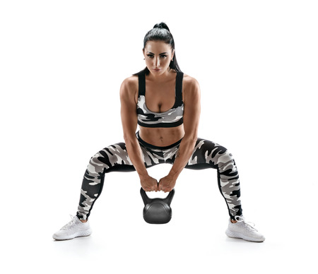 Sporty woman doing squats with kettlebell. Photo of muscular model in military sportswear isolated on white background. Strength and motivation Reklamní fotografie