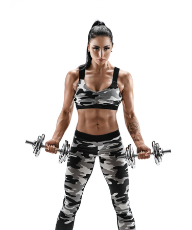 Athletic woman doing exercises with dumbbells, pumping biceps. Photo of woman in fashionable sportswear on white  background. Strength and motivation