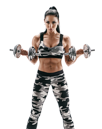 Strong muscular woman doing exercises with dumbbells, pumping biceps. Photo of latin woman in fashionable sportswear on white background. Strength and motivation