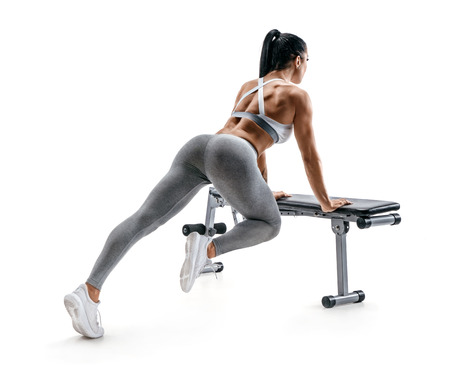 Fitness woman doing exercise leaning on sports bench. Photo of attractive latin woman in fashionable sportswear isolated on white background. Rear view. Strength and motivation