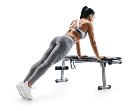 Sporty woman doing push ups on sports bench. Photo of fitness model in sportswear isolated on white background. Fitness and healthy lifestyle concept
