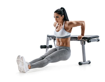 Strong woman working out arms muscles doing triceps dips using bench. Photo of latin woman with perfect body on white  background. Strength and motivation Reklamní fotografie