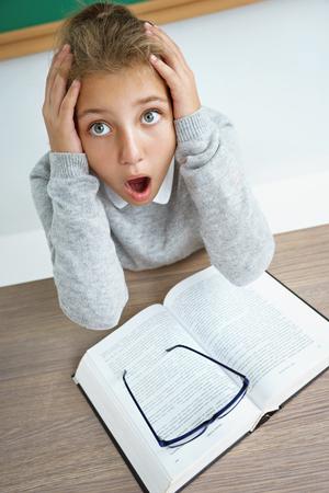 Kleines Schulmädchen, das Kopf mit geöffnetem Mund und verrücktem Gesichtsausdruck hält. Foto des Mädchens mit Buch auf dem Schreibtisch im Klassenzimmer. Zurück zur Schule