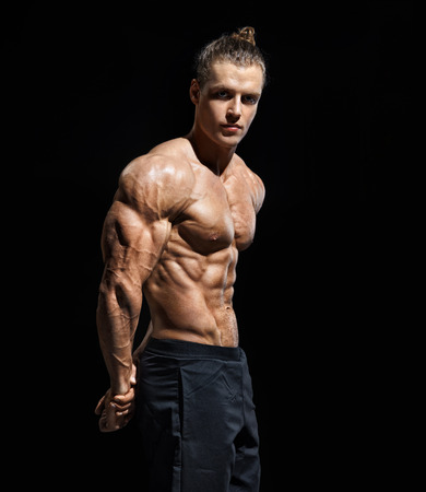 Strong athletic man posing. Photo of man with perfect physique after training on black background. Strength and motivation