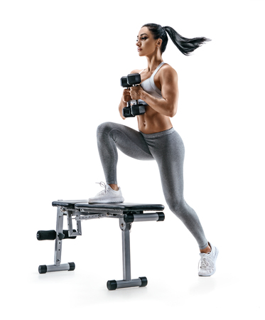 Fitness woman doing jump step ups exercise with dumbbells on bench. Photo of attractive woman in sportswear isolated on white background. Strength and motivation