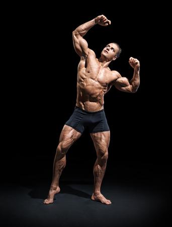 Posa atletica dell'uomo. Foto di un uomo con un fisico perfetto su sfondo nero. Forza e motivazione