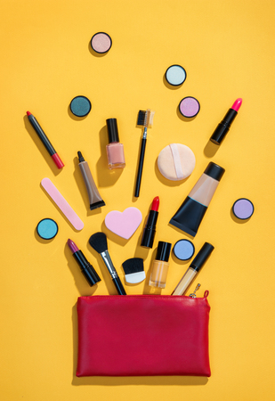 Beauty background with makeup cosmetic products. Photo of red makeup bag with cosmetic products on yellow background. Copy space for your text