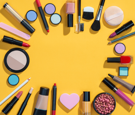 Beauty background with makeup cosmetic products. Photo of different beauty products on yellow background. Copy space for your text