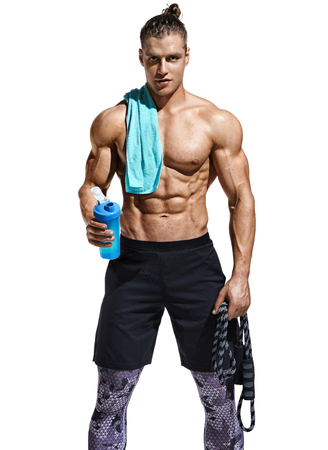 Resting time. Man with protein cocktail in shaker and towel on his shoulder. Photo of sporty man after workout with skipping rope isolated on white background. Health concept