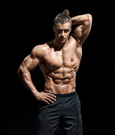 Handsome athletic man posing. Photo of young guy with perfect physique on black background. Strength and motivation