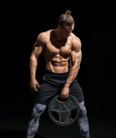 Sportive young man resting after workout with heavy weight disks. Photo of athletic man with naked torso and good physique on black background. Strength and motivation Stock Photo