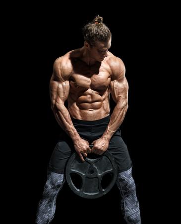 Giovane uomo sportivo allenamento con dischi pesanti. Foto di uomo con torso e fisico perfetto su sfondo nero. Forza e motivazione