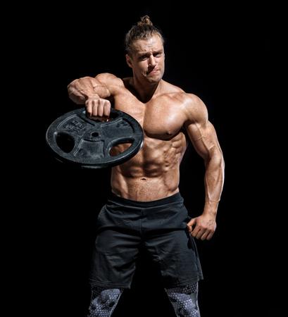 Ragazzo muscoloso che fa esercizio con dischi pesanti. Foto di giovane ragazzo con torso e buon fisico su sfondo nero. Forza e motivazione