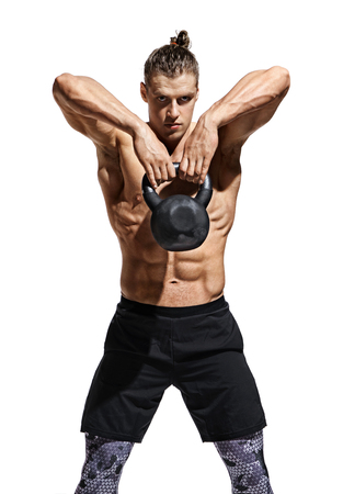 Joven musculoso entrenando con pesas rusas. Foto de hombre atlético con torso y físico perfecto sobre fondo blanco. Fuerza y motivación