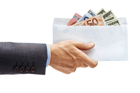 Mans hand in suit holding full envelope of money isolated on white background. High resolution product. Close up Banco de Imagens