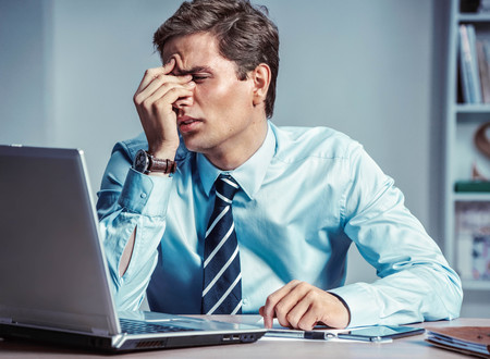 Young office man with pain in his head or an eye. Photo of man suffering from stress or a headache grimacing in pain. Business concept