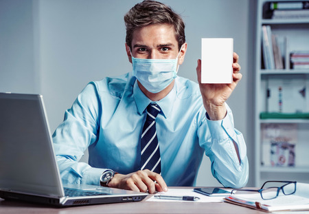 Healthy worker at the office holding white box of medicine. Photo of man wearing protective mask against infectious diseases and flu. Business and health care concept. Stock Photo