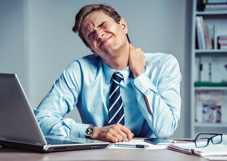 Employee suffers from severe pain in neck. Photo of man working in the office. Medical concept. Stock Photo