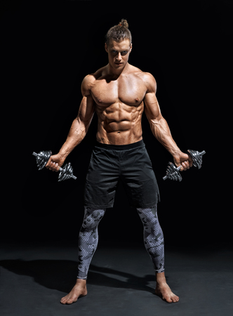 Athletic man working out with dumbbells. Photo of handsome man with good physique on black background. Strength and motivation. Full length