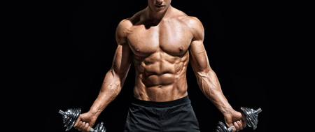 Sporty man working out with dumbbells. Photo of muscular naked torso on black background. Strength and motivation