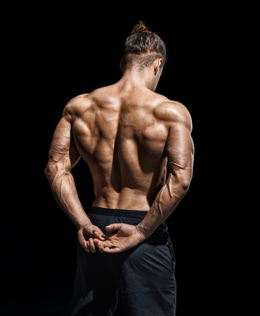 Rear view of bodybuilder with perfect physique on black background. Strength and motivation.