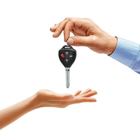 Mans hand giving the car key to womans hand isolated on white background. Close up. High resolution product
