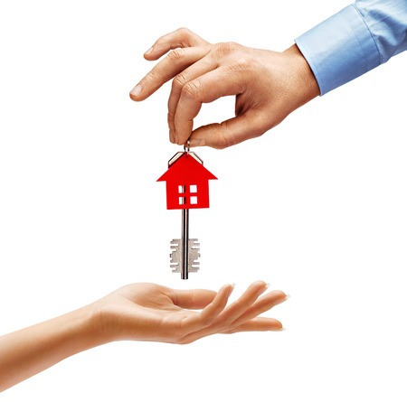 Mans hand giving the house key to womans hand isolated on white background. Close up. High resolution product