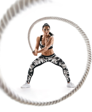 Woman doing exercises with battle rope. Photo of muscular model in military sportswear isolated on white background. Strength and motivation Stockfoto