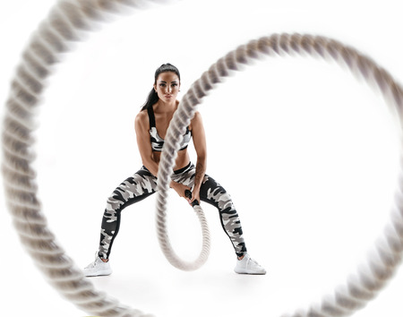 Woman doing exercises with battle rope. Photo of muscular model in military sportswear isolated on white background. Strength and motivation Stock Photo