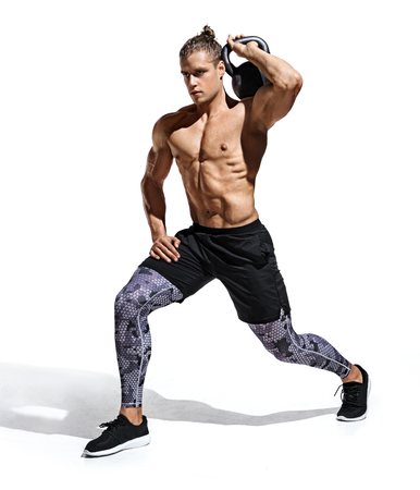 Sportive man workout with kettlebell doing lunges. Photo of handsome man with good physique isolated on white background. Strength and motivation
