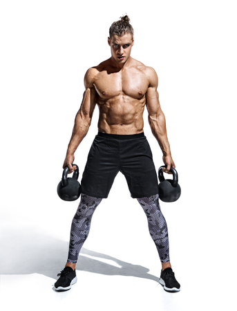 Sporty man workout with kettlebells. Photo of handsome man with naked torso and good physique on white background. Strength and motivation