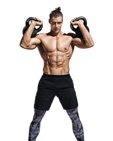 Young muscular guy training with kettlebells. Photo of sporty model with naked torso and good physique on white background. Strength and motivation