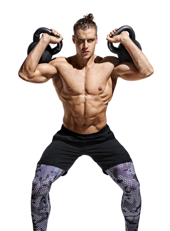 Young bodybuilder doing sit ups with heavy weight kettlebells. Photo of muscular man with naked torso and good physique on white background. Strength and motivation